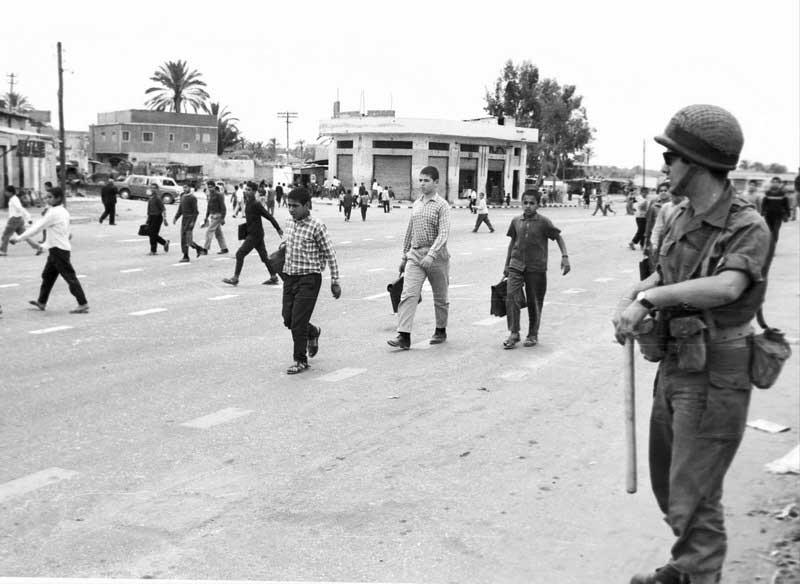 """עזה. המרחקים בין הנערים ההולכים ברחוב עם ילקוטם אינם אופייניים לאווירת החזרה מבית ספר. לאור ניסיונם ותחת מבטו המפקח של חייל האוחז בידו הימנית אלה, הנערים יודעים שרצוי להימנע מצעידה בחבורות, אם אין ברצונם להיחשד כמי שמקיימים התקהלות פוליטית. צילום: אבי שמחוני, ישראל סאן בע""""מ, 1969"""